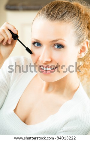 Young woman applying mascara with lash brush at home