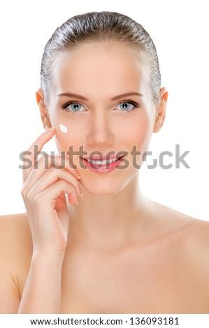 Young woman applying moisturizer - stock photo