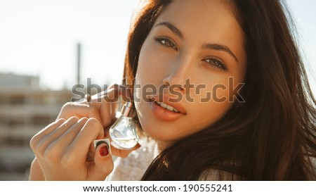 Young woman applying perfume on herself isolated on white background. Fashion photo, outdoors shot. horizontal. - stock photo