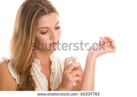 Young woman applying perfume on wrist isolated on white background - stock photo