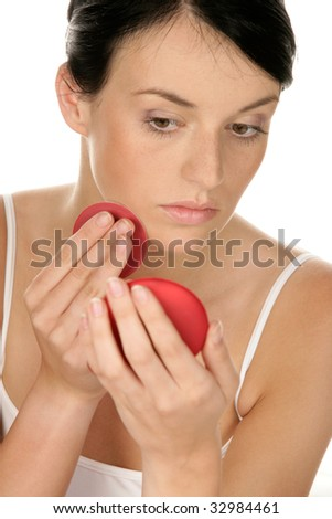 Young woman applying rouge on her cheek - stock photo