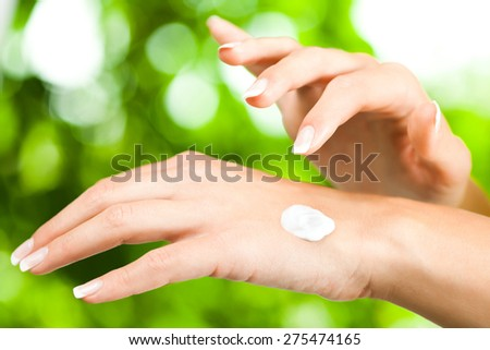 Young woman applying skin cream on her hand - stock photo