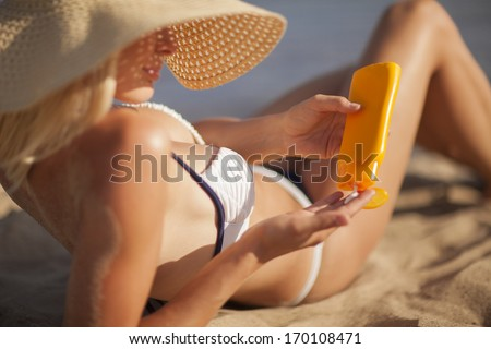 Young woman applying sunscreen on her shoulder while sitting on the beach - stock photo