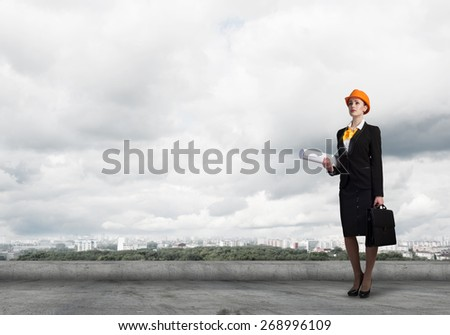 Young woman architect in hardhat holding project in hand - stock photo