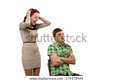 Young woman arguing with her boyfriend yelling at him as he sits in a chair with his arms folded staring upwards as he tries to control himself from retaliating, isolated on white - stock photo