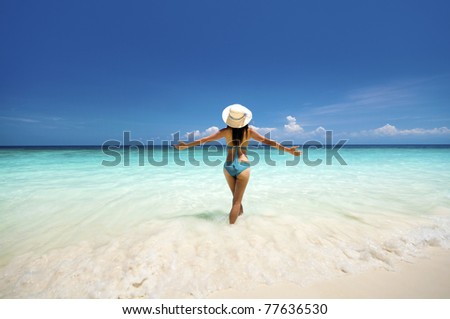 Young woman arms out enjoying the fresh air at beach - stock photo