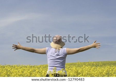 Young woman arms outstretched in a field full of bright yellow rapeseed or canola.