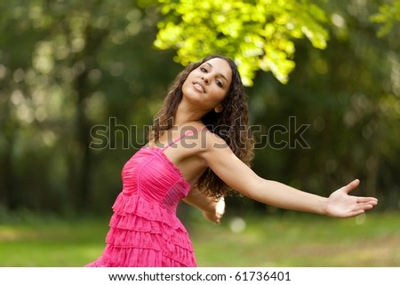 young woman arms outstretched relaxing in park