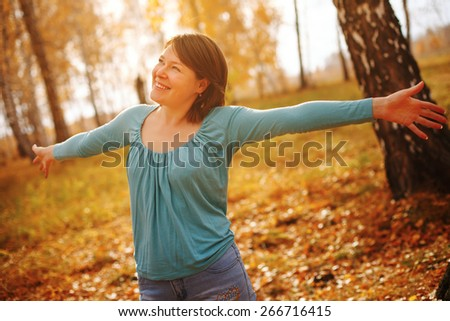 Young woman arms raised enjoying the fresh air in autumn forest. - stock photo
