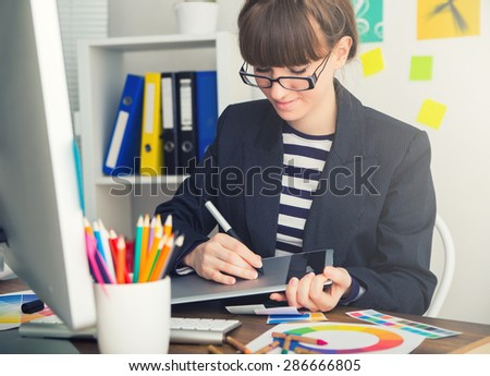 young woman artist drawing something on graphic tablet at the office - stock photo