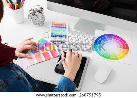 young woman artist in jeans jacket drawing something on graphic tablet at the office - stock photo