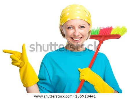 Young woman as a cleaning maid holding broom and pointing to her right, isolated over white - stock photo