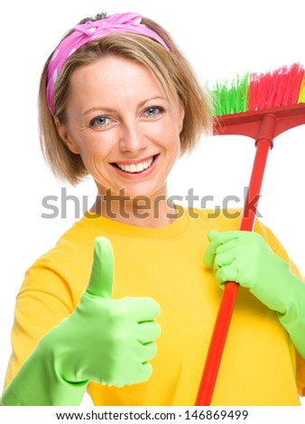 Young woman as a cleaning maid holding broom and showing thumb up gesture, isolated over white - stock photo