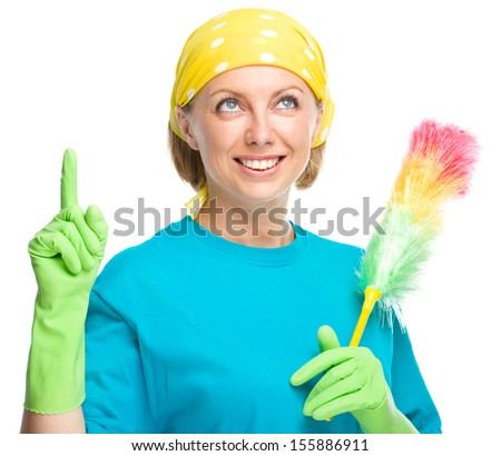 Young woman as a cleaning maid holding static duster and pointing up, isolated over white - stock photo