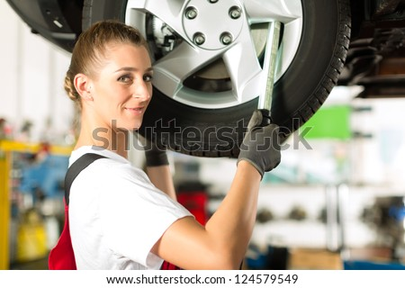 Young woman as female car mechanic working on an auto in workstation - stock photo