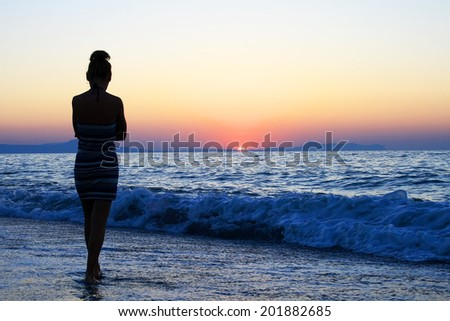 young woman as silhouette by the sea at sunset - stock photo