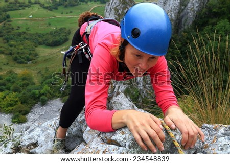 Young woman ascending a steep wall on limestone ridge - stock photo