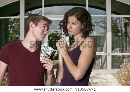 Young woman asking a man for some cash money - stock photo