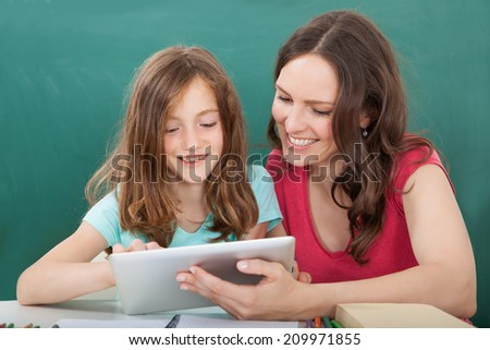 Young woman assisting girl in using digital tablet against chalkboard at home - stock photo