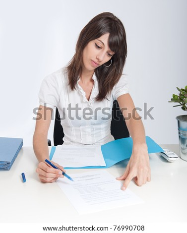 Young woman at a desk pointing a document section with her pen - stock photo