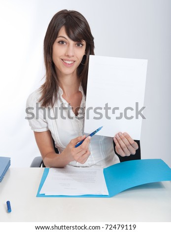 Young woman at a desk pointing with her pen to a blank paper. Ideal for inserting your own message - stock photo