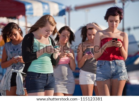 Young woman at amusement park using their phones - stock photo