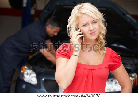 Young woman at auto repair shop - stock photo