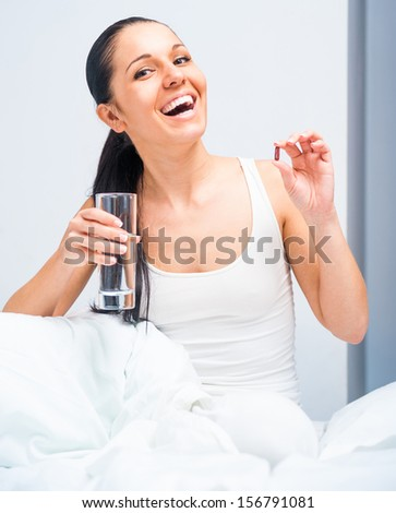 young woman at bed taking pills - stock photo