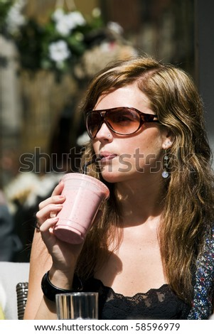 Young woman at cafe. Drinking milkshake