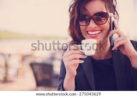 Young woman at cafe drinks coffee and talking on the mobile phone - stock photo