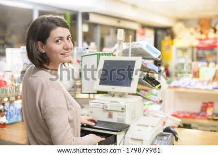 Young woman at cash register in a store - stock photo