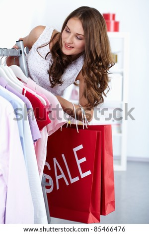 Young woman at clothing store at sales period - stock photo