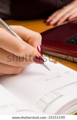 Young woman at desk writing a note (shallow dof). - stock photo