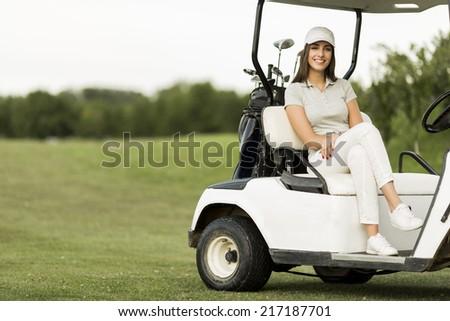 Young woman at golf cart - stock photo