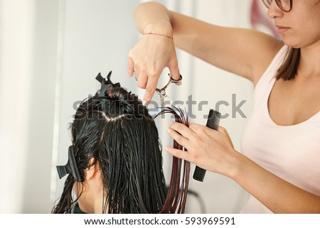 Young woman at hairdresser. Hairdresser is cutting her hair.