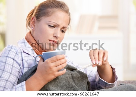 Young woman at home having flu, feeling bad, taking her temperature, drinking hot tea in bed.? - stock photo