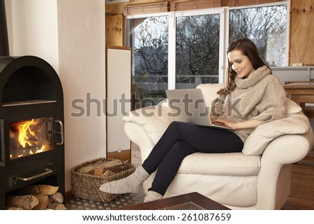 Young woman at home in chair using laptop