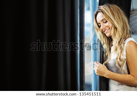 young woman at home near window - stock photo