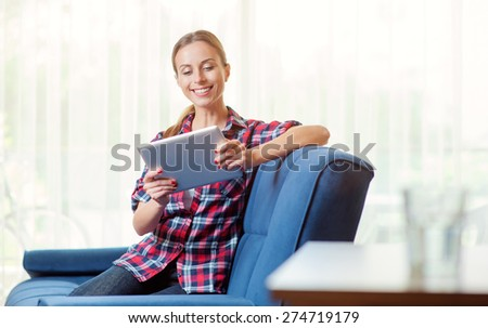 Young woman at home relaxing in her living room reading a digital tablet PC surf internet and work - stock photo