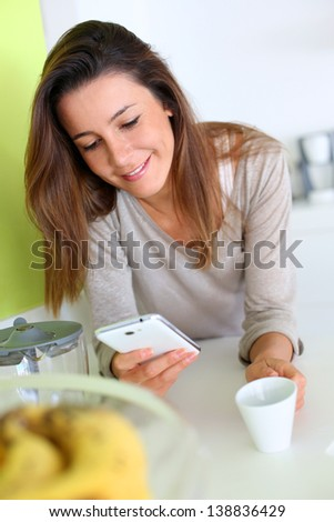Young woman at home sending message with smartphone