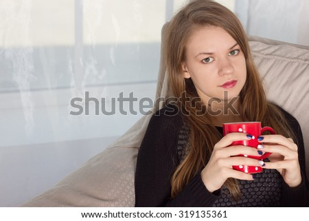 Young woman at home sitting on  chair in front of window  drinking coffee or tea - stock photo