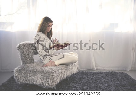 Young woman at home sitting on modern chair in front of window relaxing in her living room drinking coffee or tea reading a book.  Instagram style  - stock photo