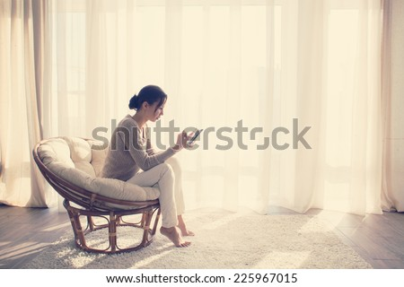 Young woman at home sitting on modern chair in front of window relaxing in her living room using tablet pc, instagram toning - stock photo