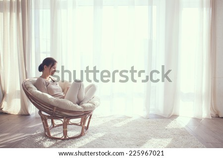 Young woman at home sitting on modern chair in front of window relaxing in her living room using tablet pc - stock photo