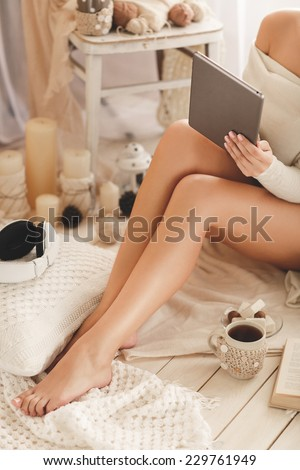 Young woman at home sitting on modern chair in front of window relaxing in her living room using tablet pc. Soft photo of woman on the bed with tablet and cup of coffee, Cozy, comfy, soft - stock photo