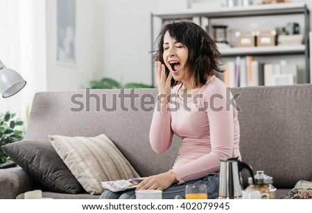 Young woman at home waking up after a bad night's sleep on the couch, she is yawning - stock photo