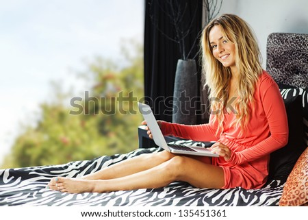 young woman at home with laptop - stock photo