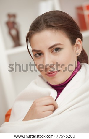 young woman at home wrapped in plaid - relaxing - stock photo