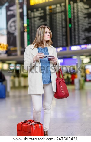Young woman  at international airport, checking electronic board and waiting for her flight. Female passenger with red suitcase and passport at arrival terminal, indoors. - stock photo