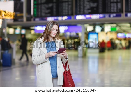 Young woman  at international airport, checking electronic board, holding passport and ticket and waiting for her flight. Female passenger at terminal, indoors. - stock photo